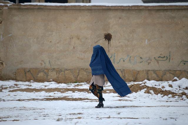 An Afghan woman walks along a street following a snowfall on the outskirts of Mazar-i-Sharif on November 23, 2016. (Photo by Farshad Usyan/AFP Photo)