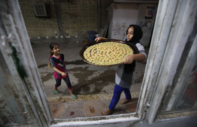An Iraqi girl carries pastries known as Kliga ahead of the Eid al-Fitr Muslim festival marking the end of Ramadan, on June 14, 2018 at a pastry shop in Baghdad. (Photo by Ahmad Al-Rubaye/AFP Photo)