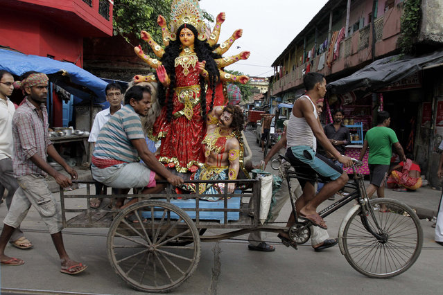 An idol of Hindu goddess Durga is transported on a cycle rickshaw to a venue of worship in Kolkata, India, Sunday, October 6, 2013. The five day Hindu festival Durga Puja is scheduled to start on October 10 and will end with the immersion of idols on October 14. (Photo by Bikas Das/AP Photo)