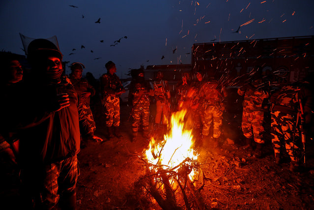 Indian soldiers warm themselves by a bonfire on a cold winter morning in Srinagar, November 29, 2016. (Photo by Danish Ismail/Reuters)
