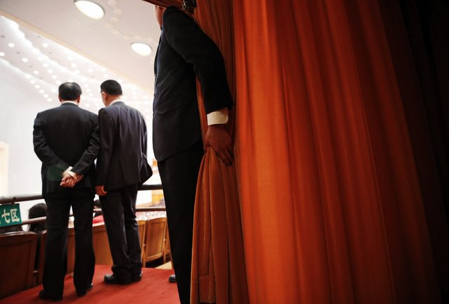 A security officer holds onto a curtain inside the Great Hall of the People during the opening session of the Chinese People's Political Consultative Conference (CPPCC) in Beijing, March 3, 2015.  REUTERS/Kim Kyung-Hoon