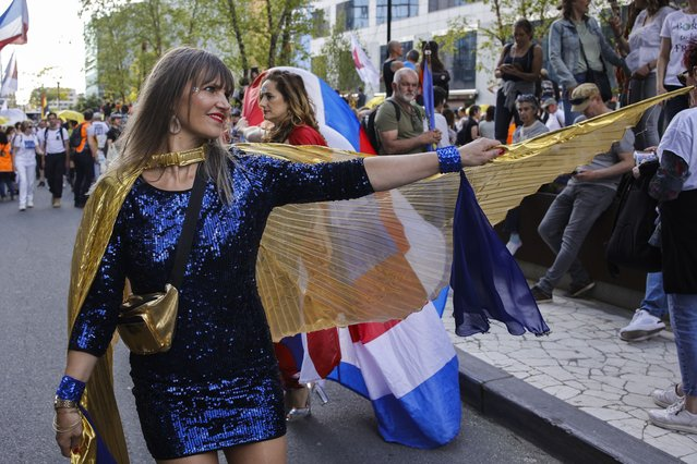 """A woman dances as people gather near EU headquarters during a so called """"European Demonstration for Freedom and Democracy"""" protest against COVID-19 security measures taken by European governments, in Brussels, Saturday, May 29, 2021. (Photo by Olivier Matthys/AP Photo)"""