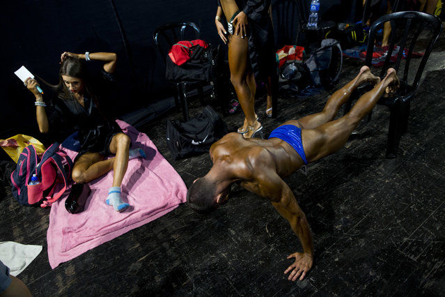 In this Thursday, October 18, 2018 photo, contestants get ready backstage during the National Amateur Body Builders' Association competition in Tel Aviv, Israel. In the run up to the flex-off, men and women, young and old, Jews and Arabs from around the country worked together to get ready for the big show. (Photo by Oded Balilty/AP Photo)