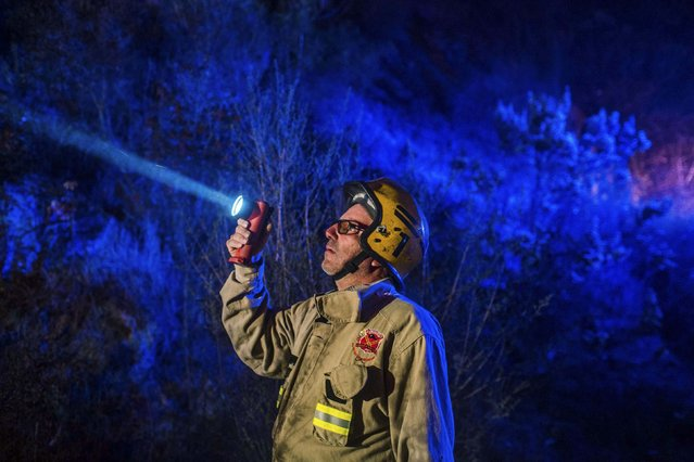 A firefighter use a lamp near a forest fire in the hills of the port city of Valparaiso, March 14, 2015. (Photo by Pablo Sanhueza/Reuters)