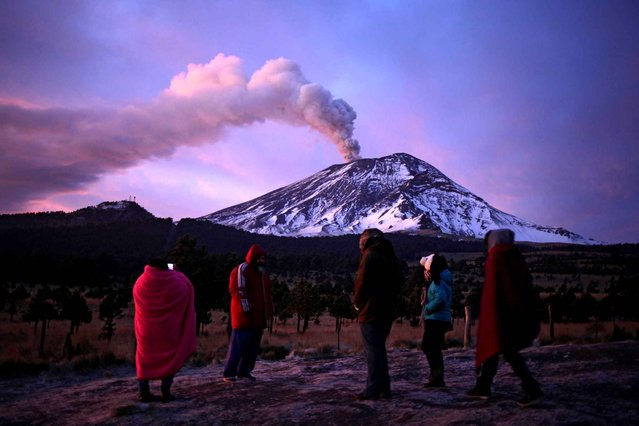 People look at the Popocatepetl volcano as it spews ash from Paso de Cortes, Puebla, Mexico on January 24, 2016. In the last hours, the monitoring system of the Popocatepetl volcano registered some explosions with large emissions of steam, gas and ash. The alert level is yellow, phase II. (Photo by Pablo Spencer/AFP Photo)