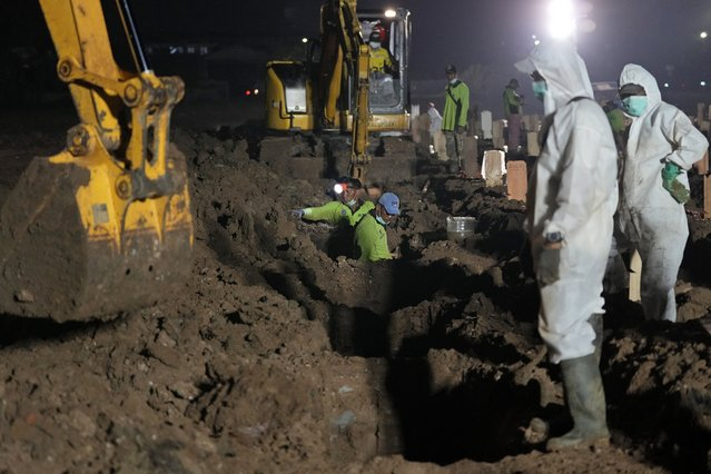 Workers dig new graves at Rorotan Cemetery which is reserved for those who died of COVID-19, in Jakarta, Indonesia, Thursday, July 1, 2021. New land around the capital city continues to be cleared for the dead and gravediggers have to work late shifts following surges in COVID-19 cases fueled by travel during the Eid holiday in May, and the spread of the delta variant of the coronavirus first found in India. (Photo by Dita Alangkara/AP Photo)