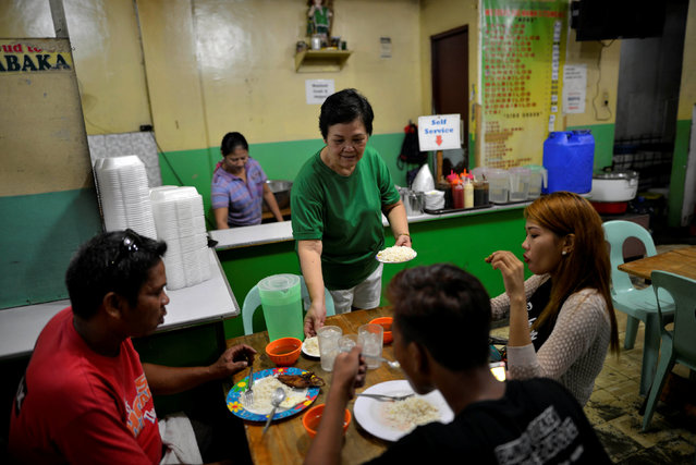 """Felicidad Magdayao, 59, owner of a fast-food restaurant serves customers in Manila, Philippines September 27, 2016. """"Our business has really suffered. People are afraid to go out. At dawn we only have few customers. At least, there are fewer drug addicts and drug pushers"""", she said. (Photo by Ezra Acayan/Reuters)"""