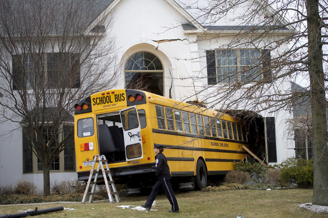 A school bus is pictured after it crashed into a house at the Windermere Development in Blue Bell, Pennsylvania March 24 2015. The school bus carrying nine elementary school students careened off the road and crashed into a occupied home in suburban Philadelphia home on Tuesday, and no injuries were reported, police said. (Photo by Mark Makela/Reuters)