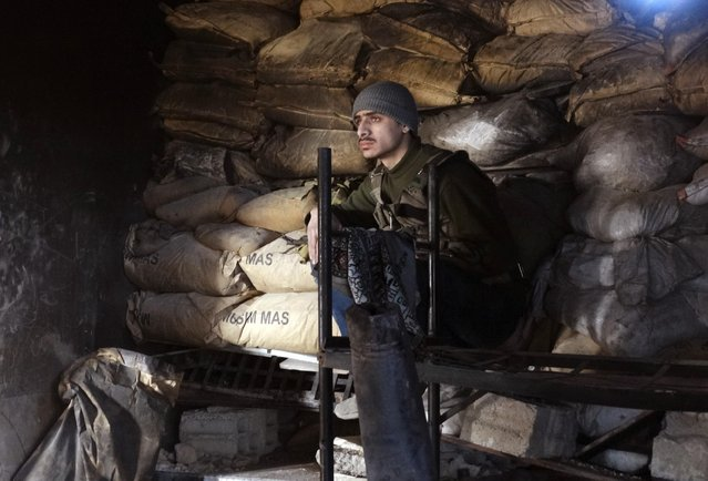 A Free Syrian Army fighter sits behind sandbags in Jobar, a suburb of Damascus January 4, 2015. (Photo by Msallam Abd Albaset/Reuters)