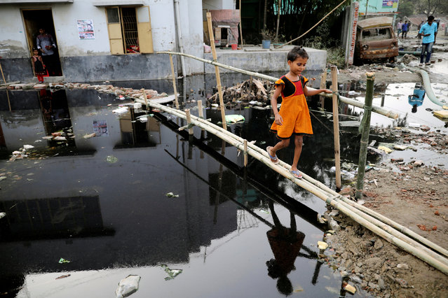 A girl walks over a bamboo bridge in front a house in Dhaka, Bangladesh November 28, 2018. (Photo by Mohammad Ponir Hossain/Reuters)