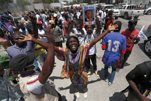 Supporters of former Haitian President Jean-Bertrand Aristide gather near the airport for his expected arrival from Cuba, where he underwent medical treatment, in Port-au-Prince, Haiti, Friday, July 16, 2021. Aristide's return adds a potentially volatile element to an already tense situation in a country facing a power vacuum following the July 7 assassination of President Jovenel Moïse. (Photo by Fernando Llano/AP Photo)