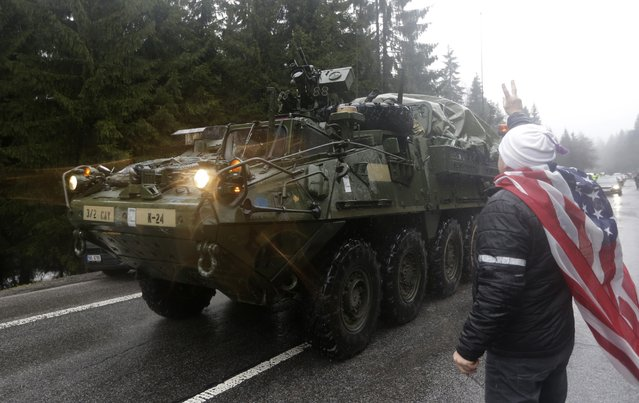 "A supporter welcomes US army convoy as it enters Czech Republic in Harrachov, Sunday, March 29, 2015. The ""Dragoon Ride"" convoy started last week from Estonia and passed through Latvia, Lithuania and Poland before entering the Czech Republic on a return journey to a German base. (Photo by Petr David Josek/AP Photo)"
