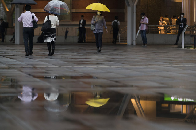 People wearing face masks walk by a train station in the rain in Tokyo on Friday, July 2, 2021. (Photo by Hiro Komae/AP Photo)