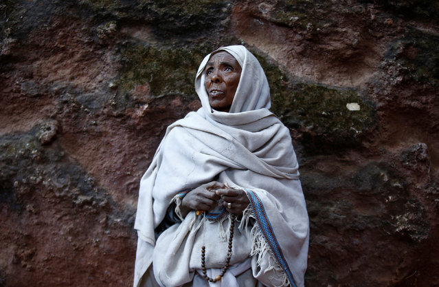 An Ethiopian Orthodox woman attends morning prayer at a rock hewn church ahead of Ethiopian Christmas in Lalibela, January 6, 2017, which is celebrated on January 7. (Photo by Tiksa Negeri/Reuters)