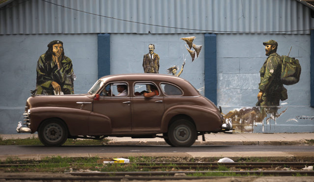 A vintage car drives by a mural showing Cuba's former leader Fidel Castro, national hero Jose Marti and revolutionary leader Che Guevara in Havana, August 2009. (Photo by Desmond Boylan/Reuters)