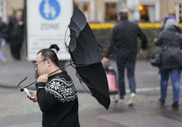A man tries to hold his umbrella in the midst of strong gusts of wind in the western German city of Cologne March 31, 2015. (Photo by Wolfgang Rattay/Reuters)