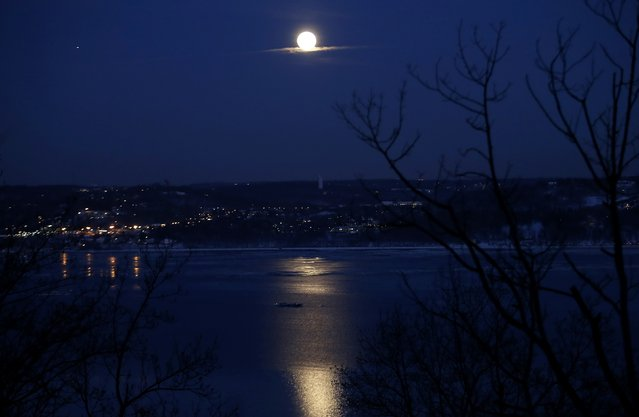 """The full """"Snow"""" moon rises above the Hudson River and the town of Irvington in Westchester County New York as seen from the west side of the Hudson in the town of Orangeburg in Rockland County, New York February 3, 2015. """"Snow"""" moon is a traditional name for the full moon that occurs in the winter month of February in North America. (Photo by Mike Segar/Reuters)"""
