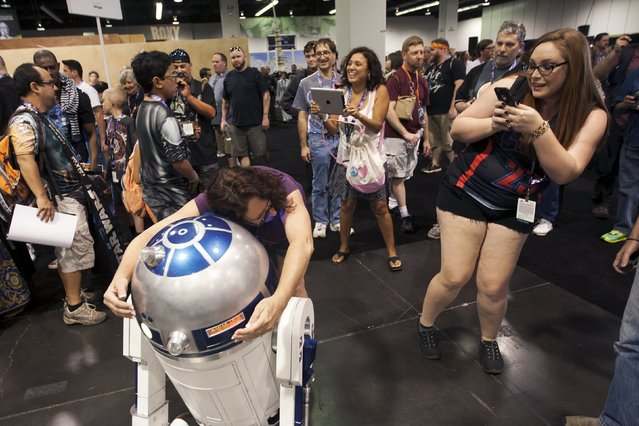 A fan hugs a R2-D2 robot character at the Star Wars celebration convention in Anaheim, California, April 16, 2015. (Photo by David McNew/Reuters)