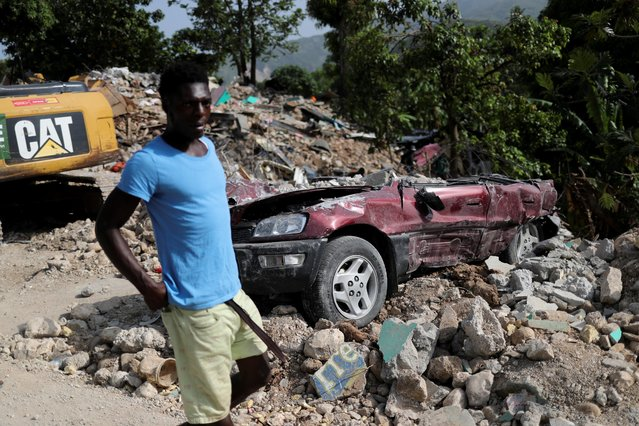 A man walks past a damaged vehicle, after the earthquake that took place on August 14, in Marceline, near Les Cayes, Haiti on August 22, 2021. (Photo by Henry Romero/Reuters)