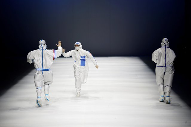 Models interact while they present protective suits made for medical professionals, designed by the Beijing Institute of Fashion Technology in collaboration with Dishang, during China Fashion Week in Beijing, China on September 11, 2021. (Photo by Tingshu Wang/Reuters)