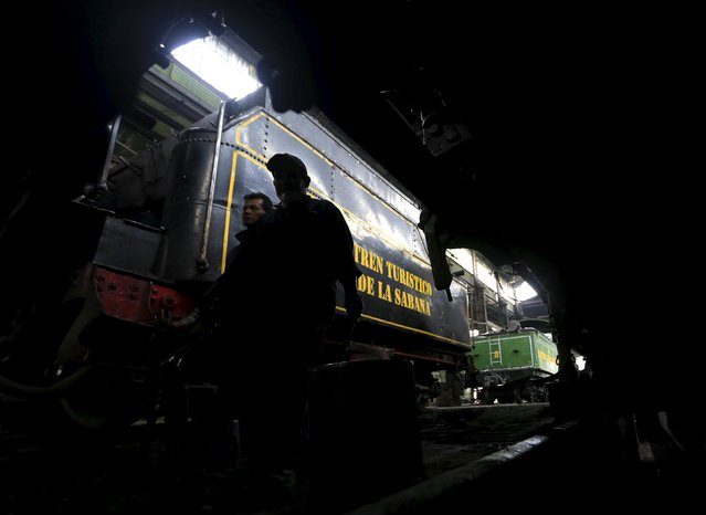 "Mechanics walk near a steam locomotive manufactured in 1934 in the ""La Sabana"" tourist train workshop in Bogota March 2, 2015. (Photo by Jose Miguel Gomez/Reuters)"