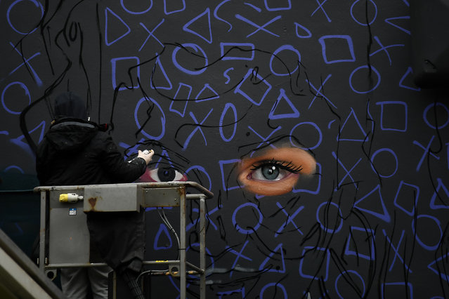 """Graffiti artist spray paints a new mural of """"Derry Girls"""" television show in Londonderry, Northern Ireland, January 25, 2019. (Photo by Clodagh Kilcoyne/Reuters)"""