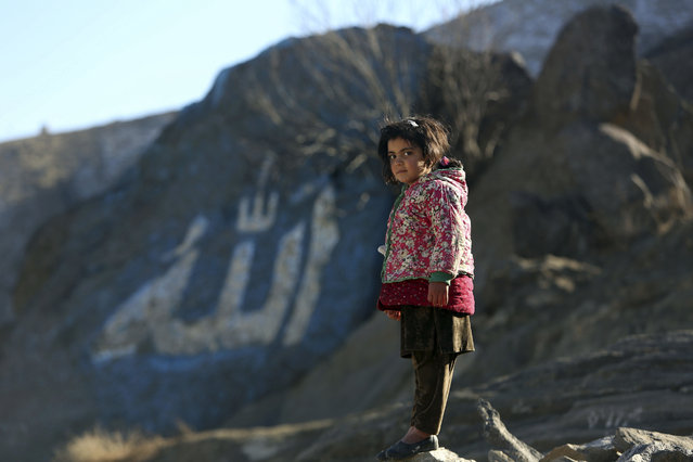 Zainab, 5, an Afghan girl, poses for photograph outside her home on the outskirts of Kabul, Afghanistan, Sunday, January 8, 2017. The Arabic word Allah, or God, is painted on a rock in the background. (Photo by Rahmat Gul/AP Photo)