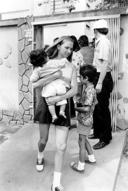 An American volunteer carries a South Vietnamese infant from a Saigon orphanage to the airport en route to the United States for adoption, Saturday, April 5, 1975. (Photo by AP Photo)
