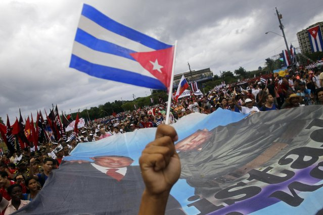 Cubans hold a a banner with an image of the late Venezuelan President Hugo Chavez and Cuban leader Fidel Castro, as they march in Revolution Square marking May Day, in Havana, Cuba, Friday, May 1, 2015. (Photo by Ramon Espinosa/AP Photo)