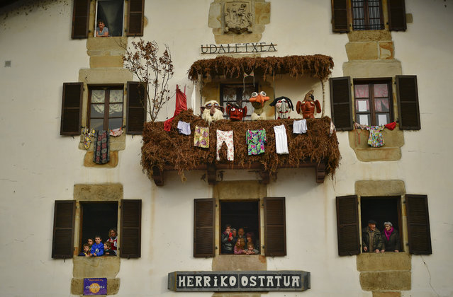 People watch from the windows of a house the Joaldunaks called Zanpantzar, during the the Carnival between the Pyrenees villages of Ituren and Zubieta, northern Spain, Monday, January 30, 2017. In one of the most ancient carnivals in Europe, dating from before the Roman empire, companies of Joaldunak (cowbells) made up of residents of two towns, Ituren and Zubieta, parade the streets costumed in sandals, lace petticoats, sheepskins around the waist and shoulders, coloured neckerchiefs, conical caps with ribbons and a hyssop of horsehair in their right hands and cowbells hung across their lower back. (Photo by Alvaro Barrientos/AP Photo)