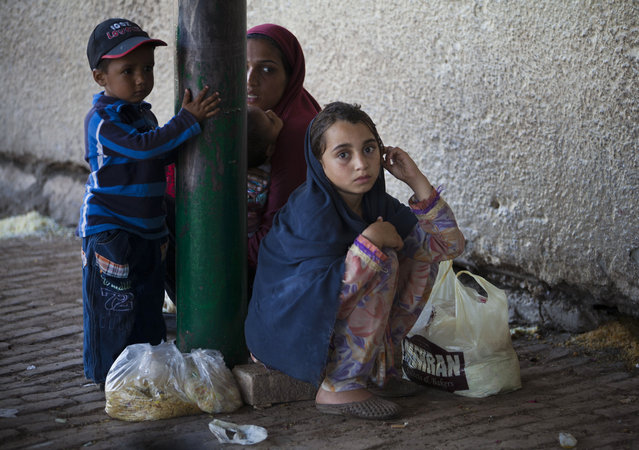 A Pakistani family waits for more food donations at a distribution center in the Barri Imam shrine in Islamabad, Pakistan, Thursday, April 23, 2015. People who visit shrines and pray that their wishes are fulfilled usually offer food to be distributed to the poor. Hundreds of poor families receive free food daily at the shrine. (Photo by B. K. Bangash/AP Photo)