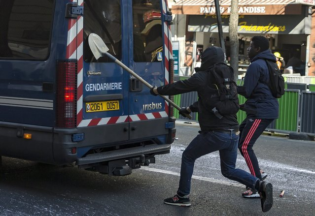 Youths attack a riot police van with a shovel as they take part in a demonstration against the government's controversial labor reform, in Paris, France, 17 March 2016. French students are protesting against a draft of the French government on new labor laws. (Photo by Etienne Laurent/EPA)