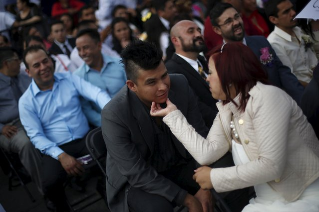 A bridal couple speak to each other while they wait before a mass wedding ceremony in which 2,016 couples participated, at Zocalo square in Mexico City, Mexico, March 19, 2016. Thousands of couples took part in a mass wedding ceremony Saturday in Mexico City. More than 5,000 people descended on Mexico City's central square for the festivities. Among them were 2,165 couples ready to get married. Sitting in front of a large stage, the couples were asked if they would like to marry each other. (Photo by Edgard Garrido/Reuters)