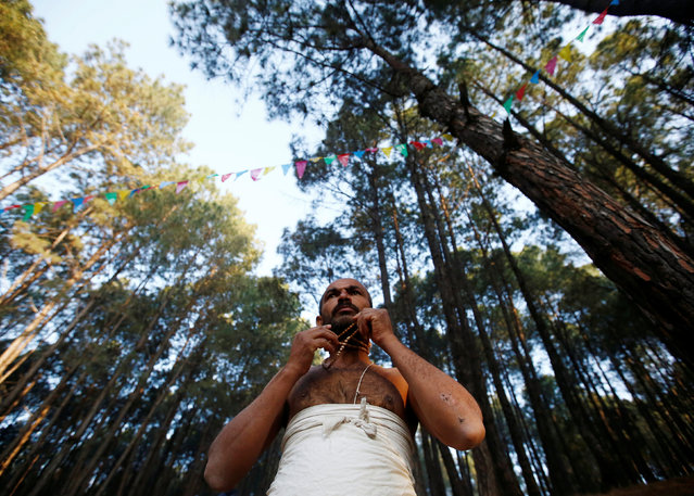 A devotee prepares to perform religious rituals during the Swasthani Bratakatha festival in the woods of Changu Narayan in Bhaktapur, Nepal February 8, 2017. (Photo by Navesh Chitrakar/Reuters)