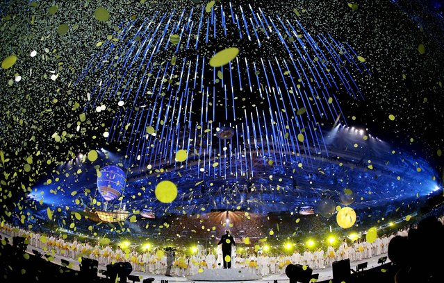 Confetti streams from the ceiling as artists perform. (Photo by Darron Cummings/Associated Press)