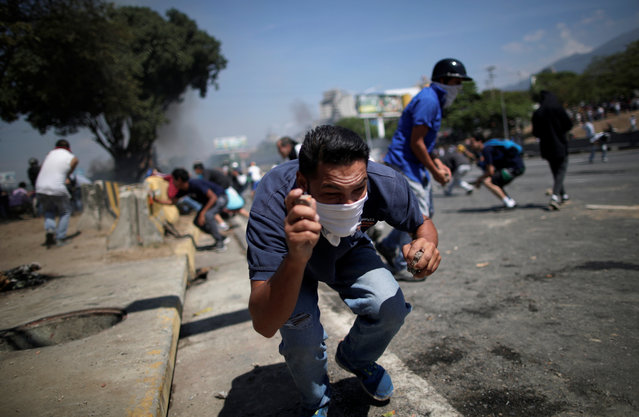 "An opposition demonstrator crouches down, holding rocks, on a street near the Generalisimo Francisco de Miranda Airbase ""La Carlota"", in Caracas, Venezuela April 30, 2019. (Photo by Ueslei Marcelino/Reuters)"