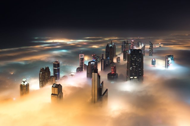 This breathtaking view from the world's tallest building shows a thick blanket of smoggy fog smother Dubai. (Photo by Bjoern Lauen/Solent News & Photo Agency)