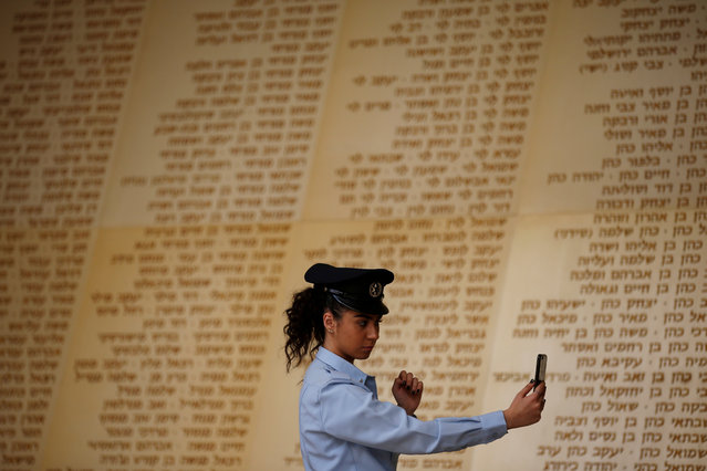An Israeli policewoman looks at her phone as she stands in front of a monument engraved with names of fallen Israeli soldiers, before a ceremony marking Memorial Day, which commemorates the fallen soldiers of Israel, at a monument in Jerusalem on May 7, 2019. (Photo by Ronen Zvulun/Reuters)