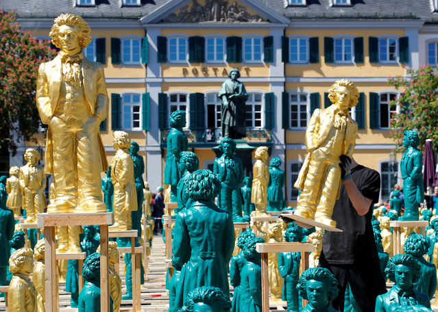 A Ludwig van Beethoven sculpture overlooks the Muensterplatz square as a worker sets up one of hundreds of Beethoven plastic sculptures designed by German conceptual artist Ottmar Hoerl to mark the 250th birth anniversary of German composer, who was born in the city, in Bonn, Germany May 15, 2019. (Photo by Wolfgang Rattay/Reuters)