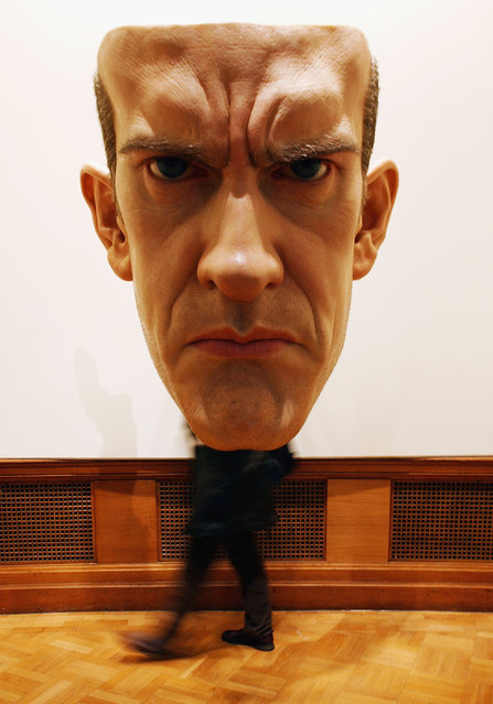 "An unidentified man walks behind Ron Mueck's ""Mask"" at a press preview of Charles Saatchi's new gallery in the former GLC building County Hall, April 14, 2003 in London, England. (Photo by John Li/Getty Images)"