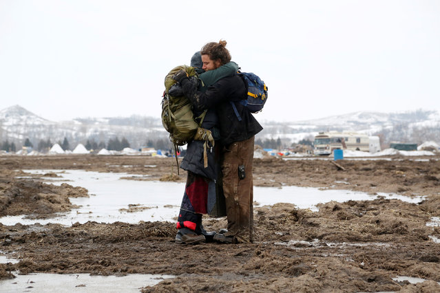 Susanna Travis (left), from Grass Valley, California, embraces Timothy Powers, also from California, before evacuating the main opposition camp against the Dakota Access oil pipeline near Cannon Ball, North Dakota, U.S., February 23, 2017. (Photo by Terray Sylvester/Reuters)