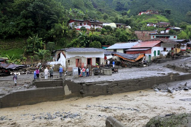 Residents stand in front of their damaged houses, after a landslide sent mud and water crashing onto homes close to the municipality of Salgar in Antioquia department, Colombia May 19, 2015. (Photo by Jose Miguel Gomez/Reuters)