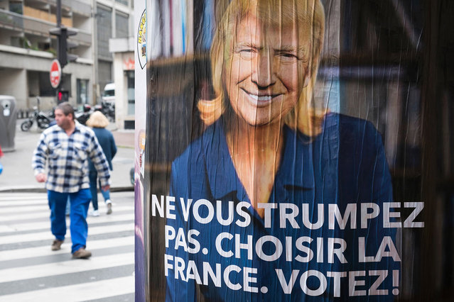 "A man passes a poster depicting French presidential election candidate for the far-right Front National (FN) party Marine Le Pen with the face of U.S. President Donald Trump reading ""Do not Trump yourself. Choose France. Vote!"" on May 5, 2017 in Paris. (Photo by Joel Saget/AFP Photo)"
