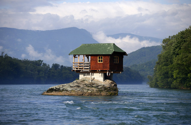 A house built on a rock is seen on the river Drina near Bajina Basta, Serbia May 22, 2013. The house was built in 1968 by a group of young men who decided that the rock on the river was an ideal place for a tiny shelter, according to the house's co-owner, who was among those involved in its construction. (Photo by Marko Djurica/Reuters)