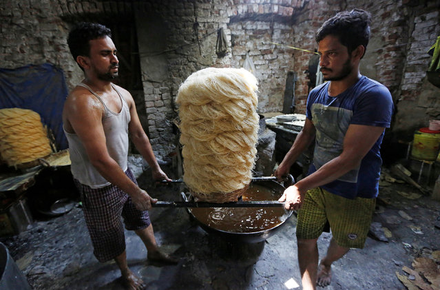 Men carry vermicelli, a specialty eaten during the Muslim fasting month of Ramadan, at a factory in Kolkata, India on May 27, 2019. (Photo by Rupak De Chowdhuri/Reuters)