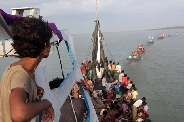 Boats of Acehnese fishermen (in front) tow a boat of Rohingya migrants in their boat off the coast near the city of Geulumpang in Indonesia's East Aceh district of Aceh province before being rescued on May 20, 2015. Hundreds of starving boatpeople were rescued off Indonesia on May 20 as Myanmar for the first time offered to help ease a regional migrant crisis blamed in part on its treatment of the ethnic Rohingya minority. (Photo by AFP Photo/Stringer)