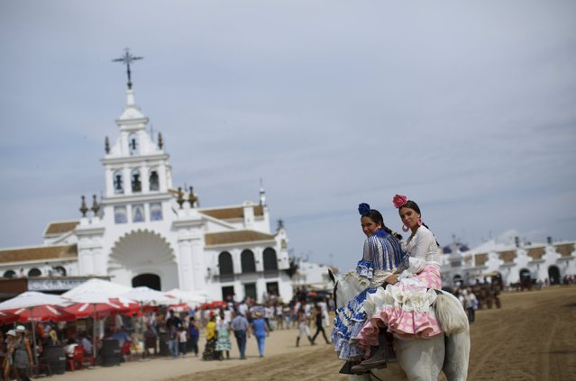 Pilgrims smile as they ride a horse in front of the shrine of El Rocio in Almonte, southern Spain May 24, 2015. (Photo by Marcelo del Pozo/Reuters)