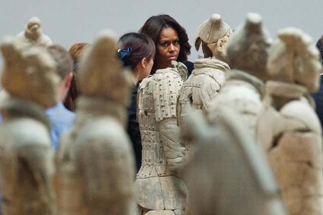 U.S. first lady Michelle Obama, center, checks Terracotta Warriors as she visits Qinshihuang Terracotta Warriors and Horses Museum with her daughters and her mother in Xi'an in northwestern China's Shaanxi province, Monday, March 24, 2014. (Photo by Alexander F. Yuan/AP Photo)