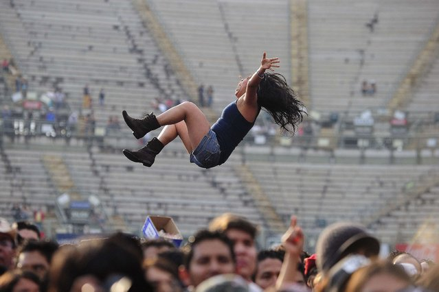 People are seen in the crowd as Serbian Emir Kusturica & The No Smoking Orchestra performs during the third day of the Mexican musicial festival Vive Latino, at the Foro Sol in Mexico City, on March 29, 2014. (Photo by Alfredo Estrella/AFP Photo)
