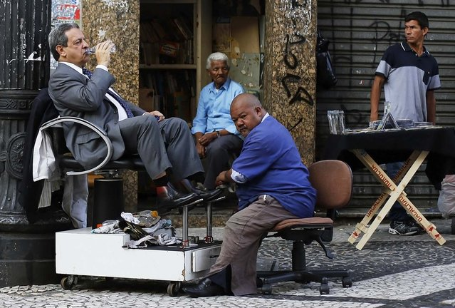 A customer drinks a bottle of water as his shoes are polished by a shoe shiner on a street in downtown Sao Paulo April 8, 2014. (Photo by Nacho Doce/Reuters)